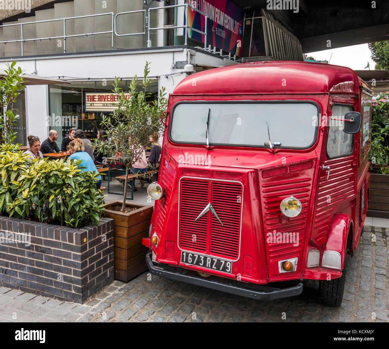 A vintage Citroen H panel van, painted red and parked outside a bar / restaurant on the South Bank, London, England, UK. Stock Photo