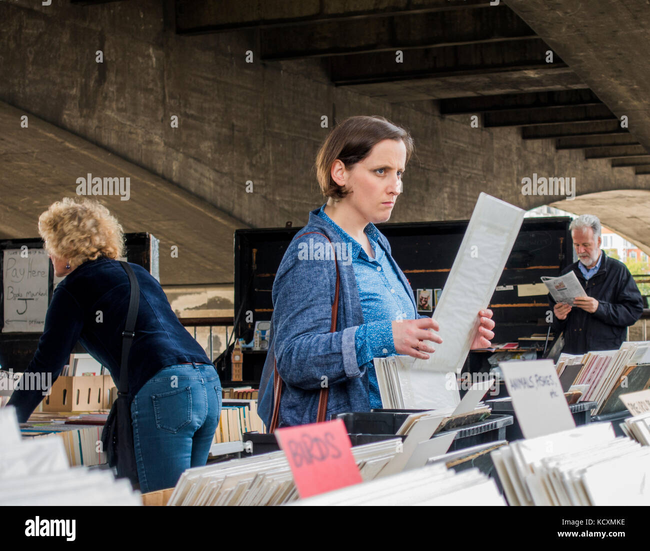 Woman thinking / lost in thought, holding a print at South Bank / Southbank book market, under Waterloo Bridge over - Stock Image