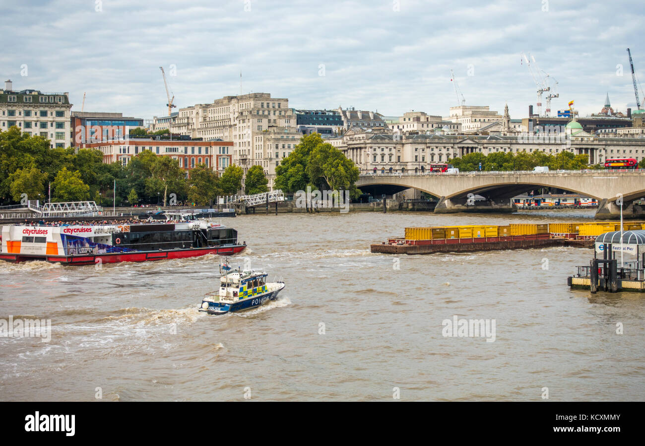 The Marine Police Force, (Thames River Police) Fast Response boat in hot pursuit of a loaded barge heading up the - Stock Image