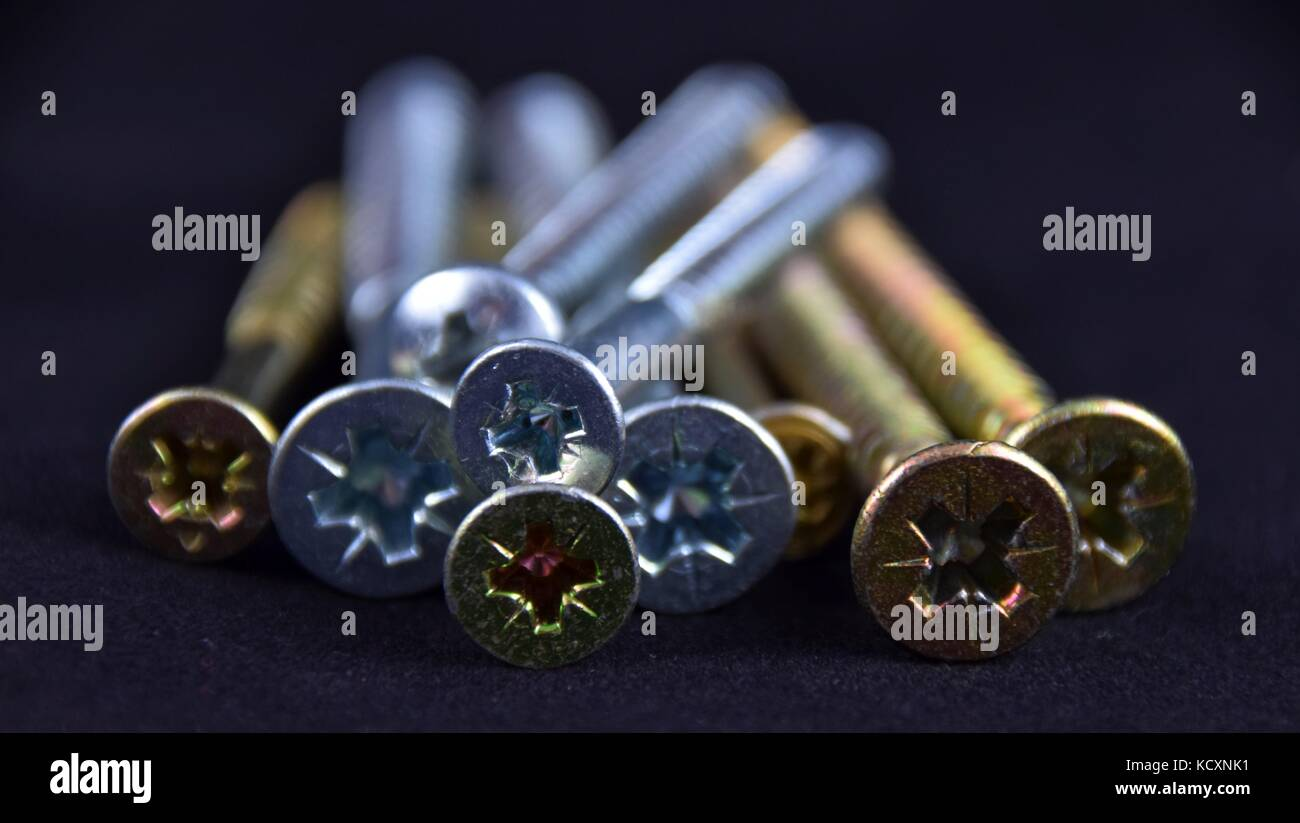 Abstract cross-head or Phillips-head or recessed-head screw on black Background, - Stock Image