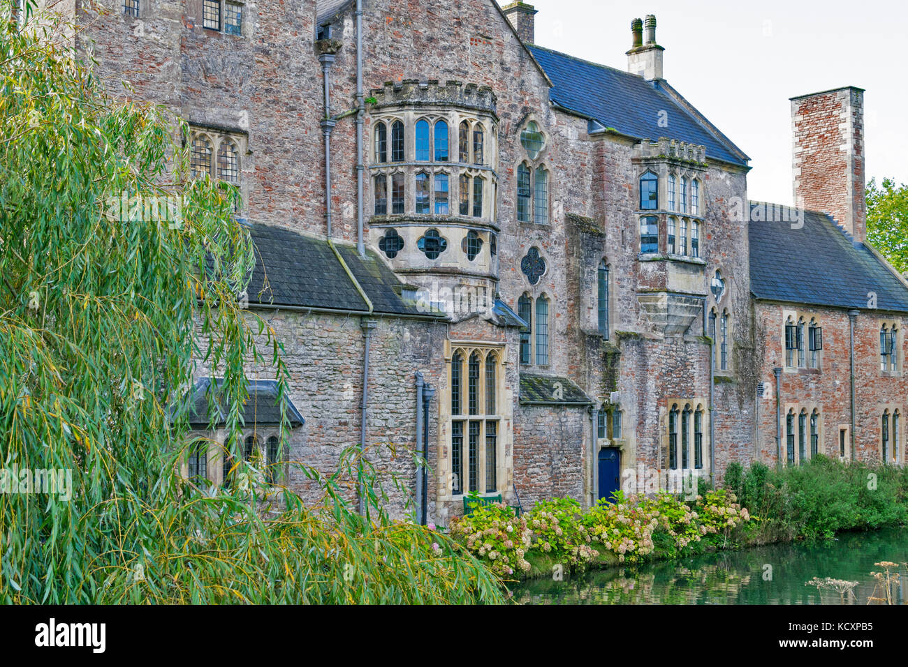 WELLS SOMERSET ENGLAND THE  BISHOPS PALACE VIEW OF WALL WITH MANY TYPES OF WINDOW OVERLOOKING THE MOAT - Stock Image