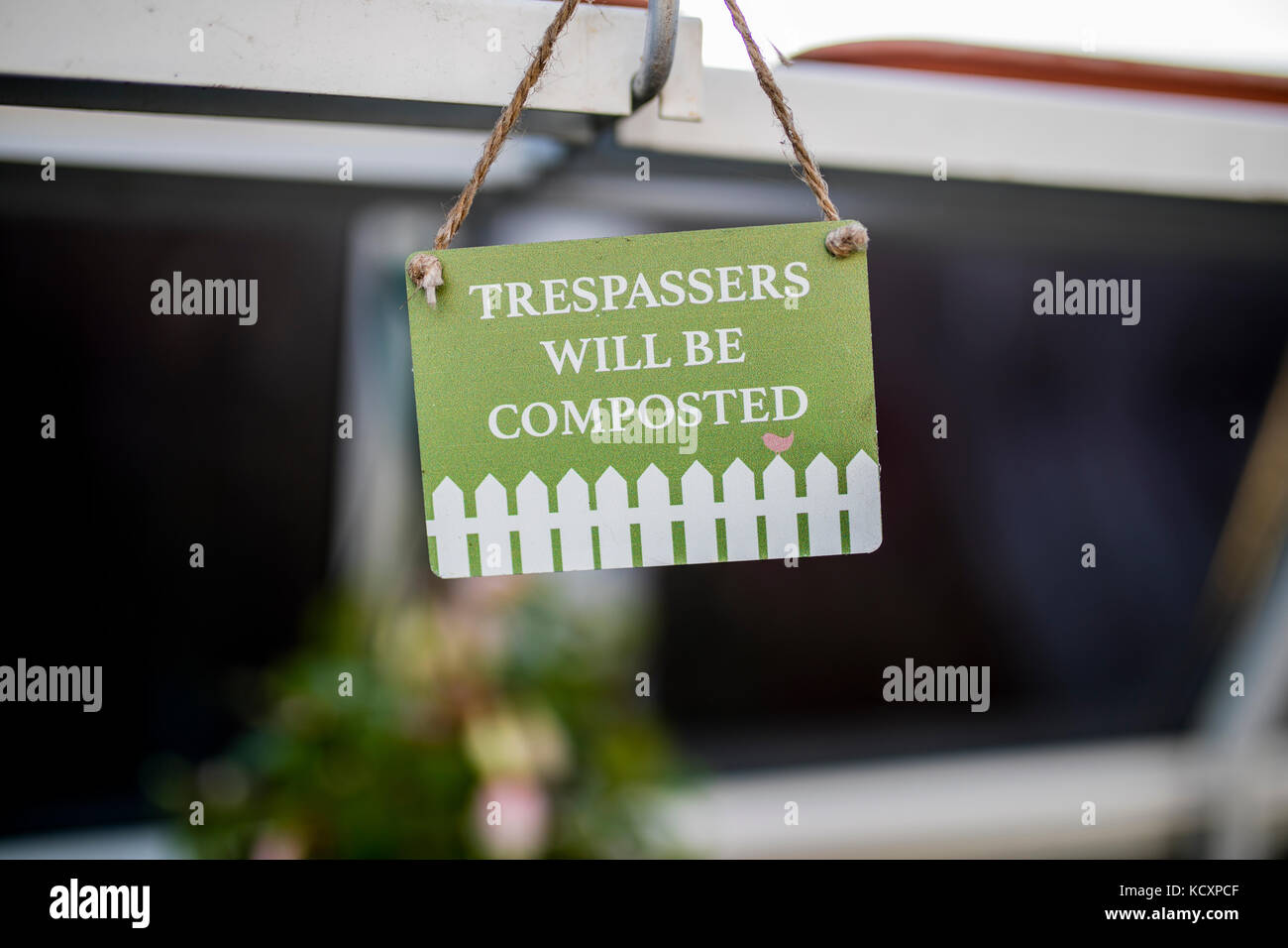 Trespassers will be composted quirky and humourous gardening sign hanging in an English green house or potting shed - Stock Image