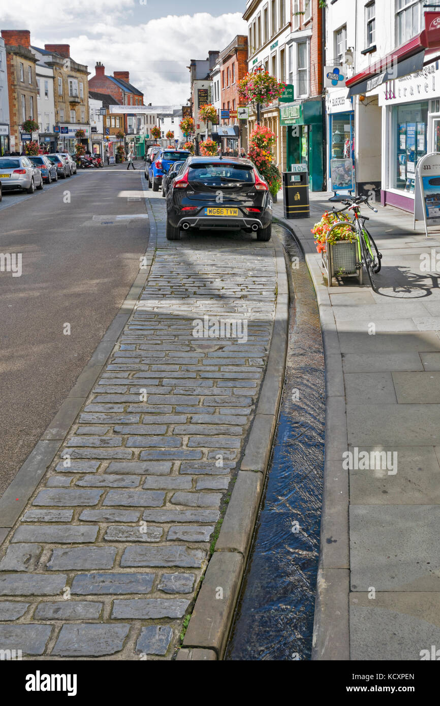 WELLS SOMERSET ENGLAND THE MAIN STREET LEADING TO THE CATHEDRAL WITH PERMANENT WATER IN RILLS OR DRAINS FROM THE - Stock Image