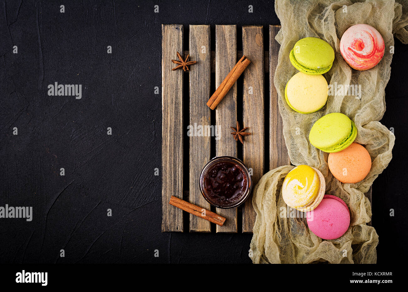 Colorful macaroons and a  jar of honey on a wooden background. Flat lay. Top view Stock Photo