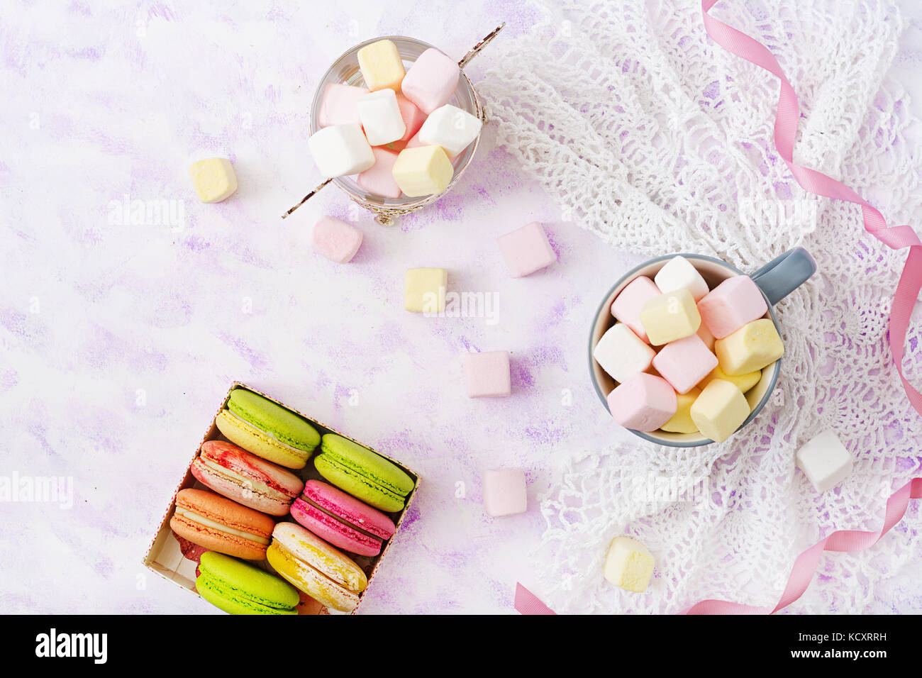 Colorful macaroons and marshmallows on a light background. Flat lay. Top view - Stock Image