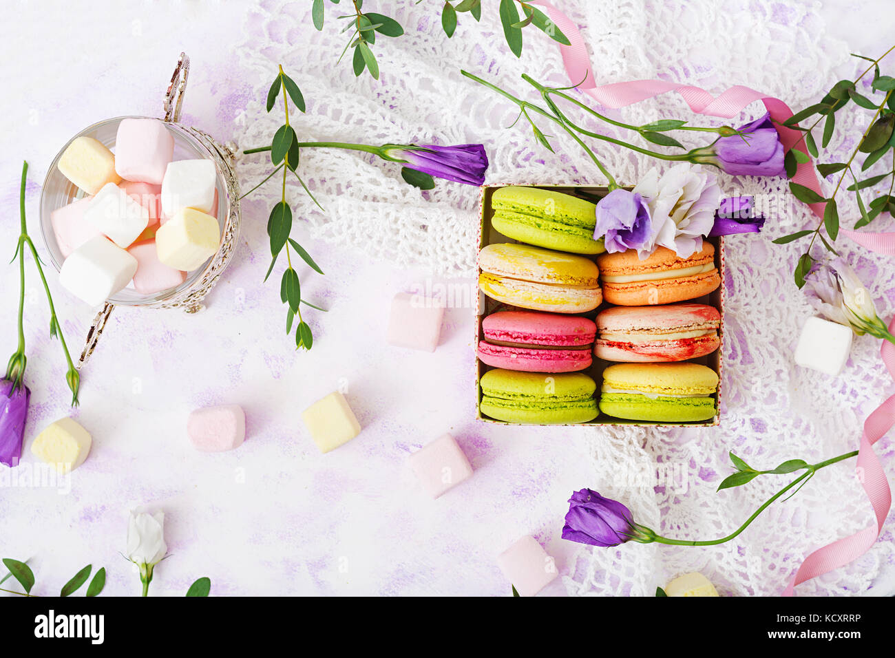 Colorful macaroons and marshmallows on a ligth  background. Flat lay. Top view - Stock Image