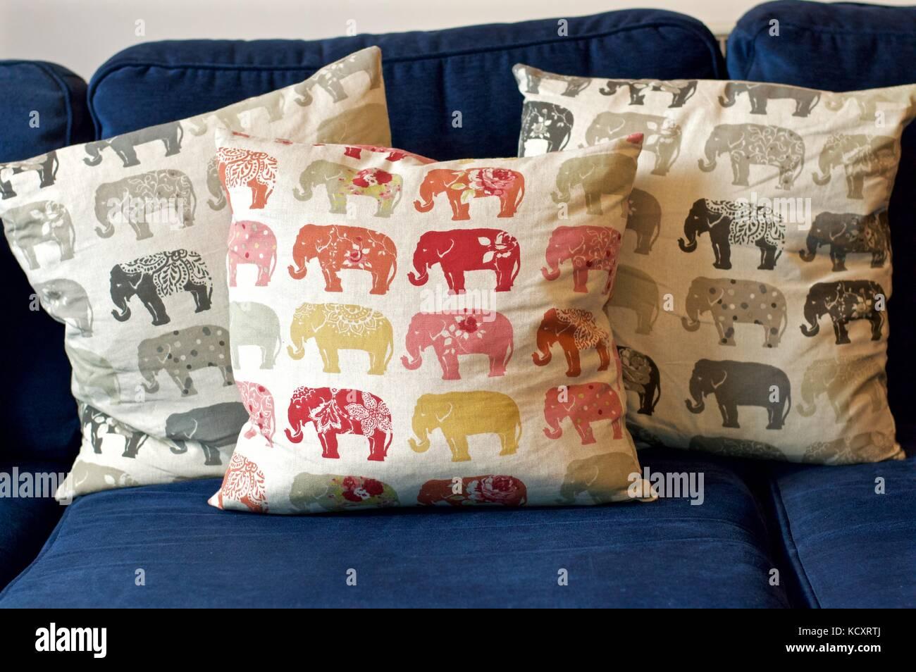 Elephant patterned cushions on blue sofa - Stock Image