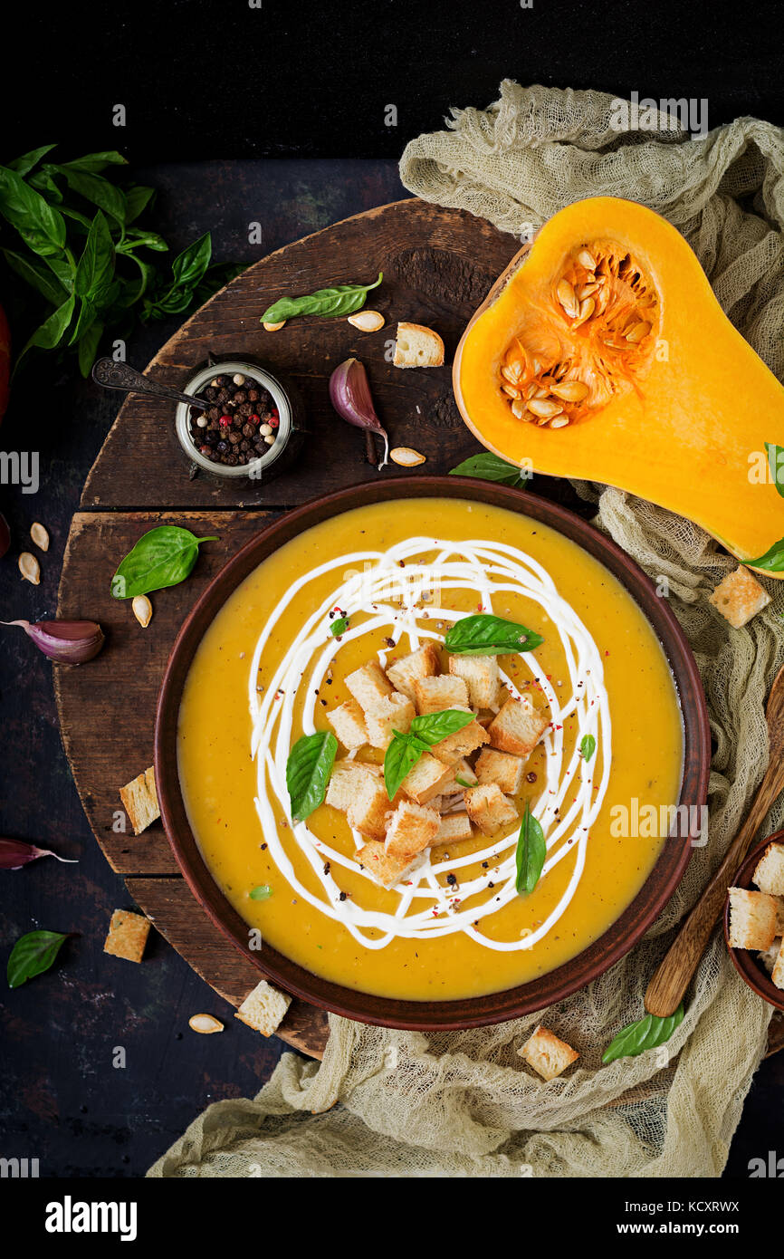 Cream of pumpkin soup with sour cream sauce. Flat lay. Top view - Stock Image