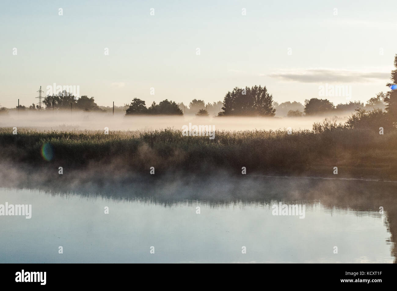 Fog covered grass field  near the lake. Dreamy reflections on a ponds surface. - Stock Image