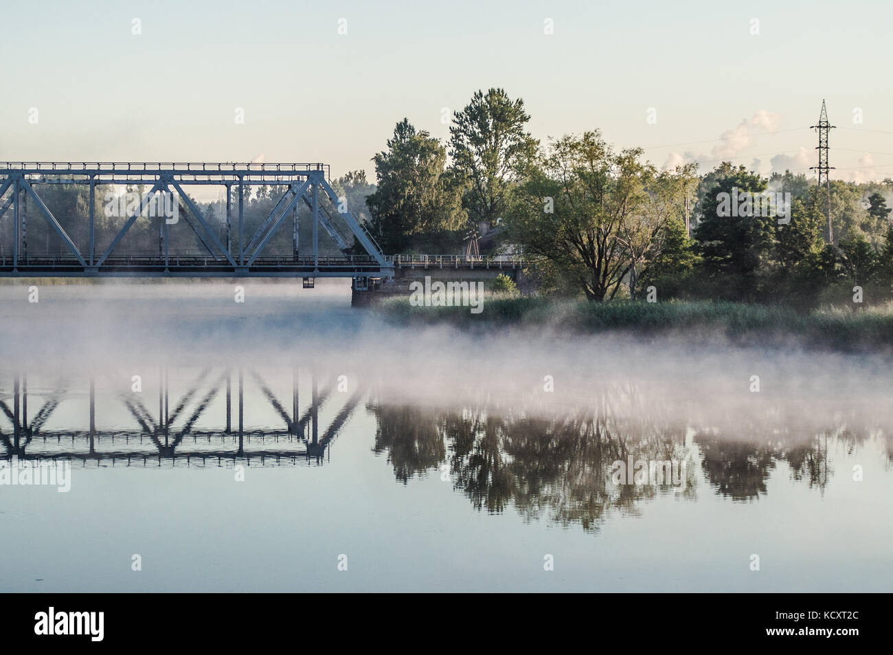 Railway bridge above misty lake. Reflection on water surface. - Stock Image