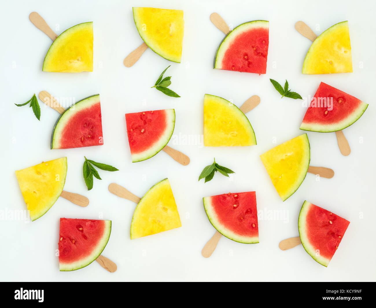 Red and yellow watermelon slices on wooden sticks with mint leaves among them on a white background. Flat lay, top - Stock Image
