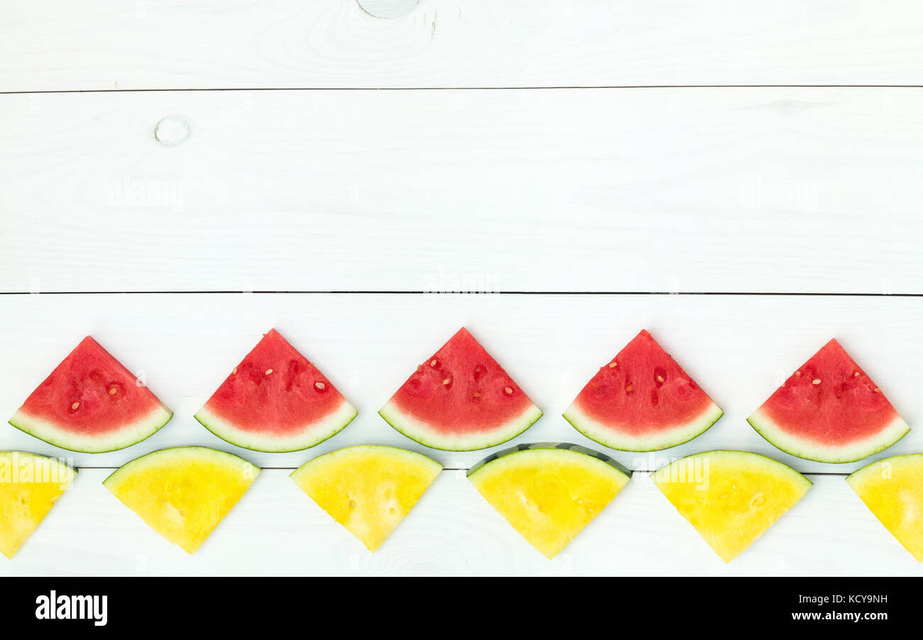 Red and yellow watermelon slices on wooden sticks on a white wooden background. Flat lay, top view, copy space - Stock Image