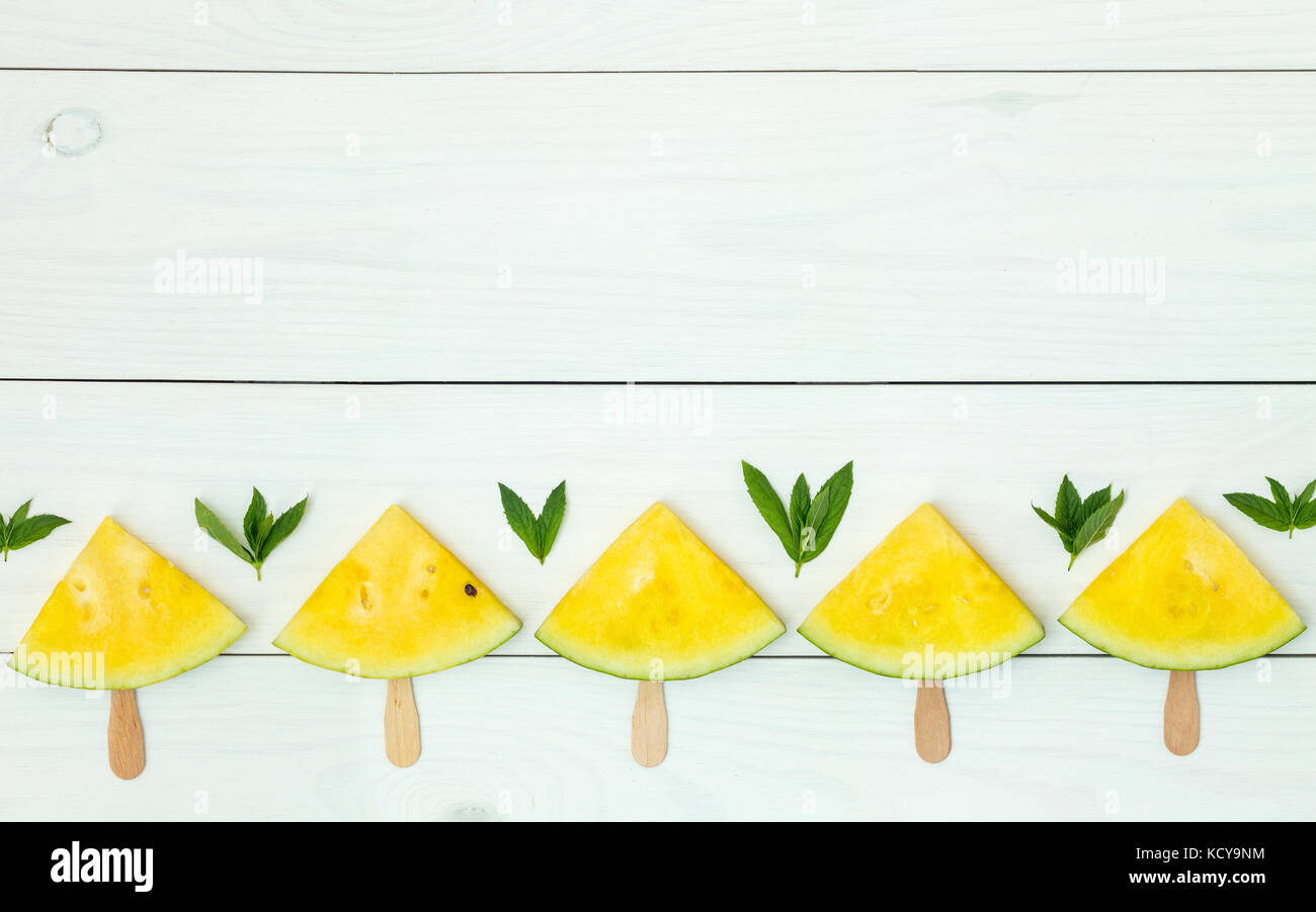 Bright yellow watermelon slices on wooden sticks on a white wooden background. Flat lay, top view, copy space - Stock Image