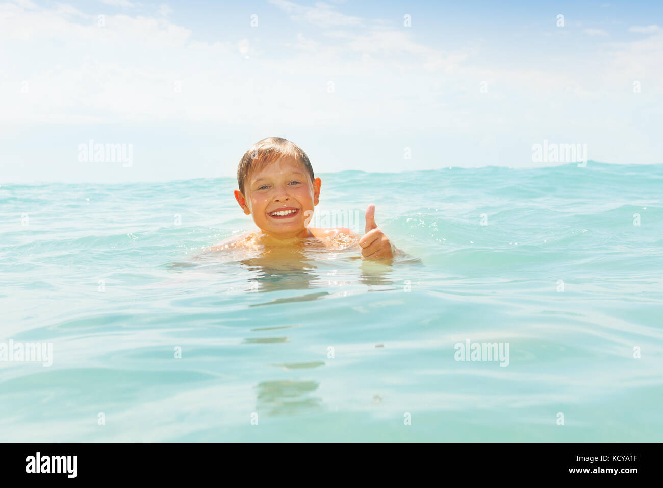 Happy preteen boy swimming in the sea, having fun and showing thumb up - Stock Image
