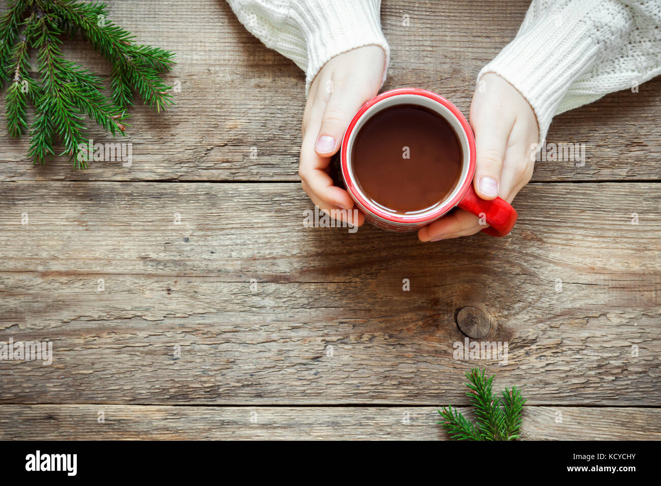 Female Hands Holding Red Mug Of Hot Chocolate Coffee On Rustic Wooden Background With Cristmas Fir Tree Branch Copy Space Cozy Homemade Winter