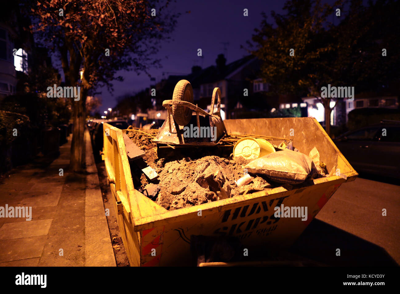 Wheelbarrow on a skip at night     picture by Gavin Rodgers/ Pixel8000 - Stock Image