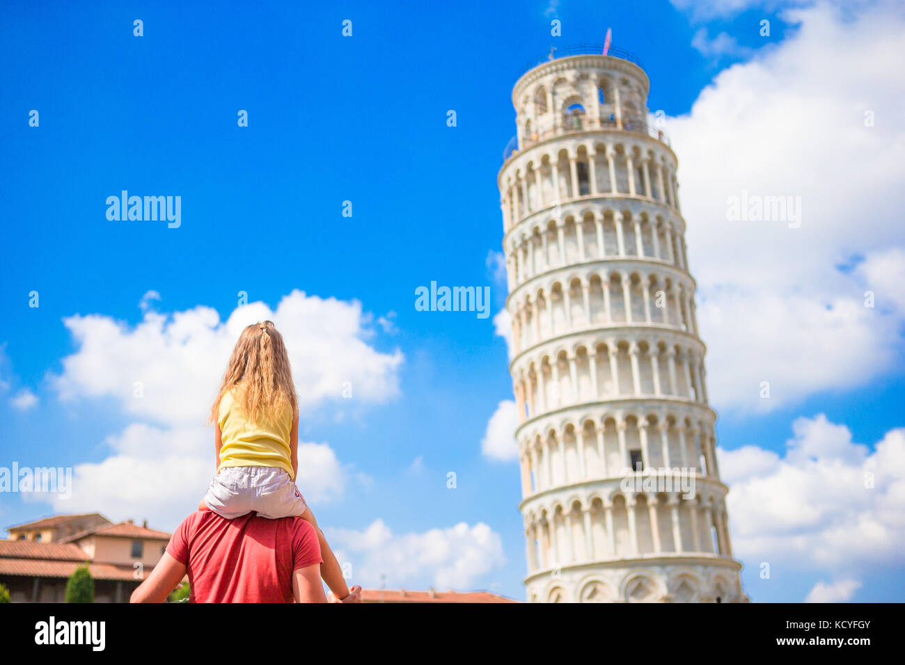 Pisa - travel to famous places in Europe, family portrait in background the Leaning Tower in Pisa, Italy - Stock Image