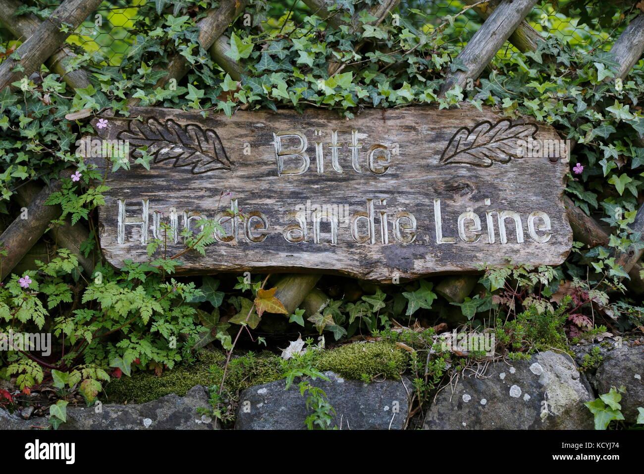 Holzschild mit Schrift Bitte Hunde an die Leine - Stock Image