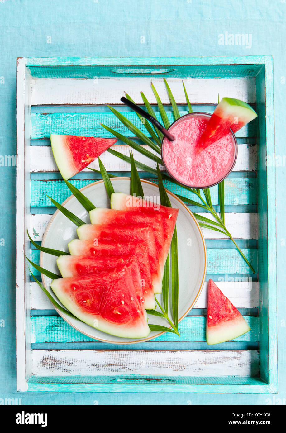 Watermelon smoothie, fresh juice on colorful wooden background with palm leaves. Top view. Copy space. - Stock Image