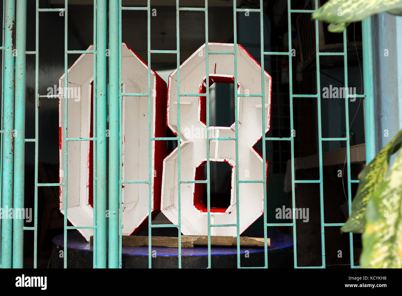 Numbers '08' zero eight 3 dimensional signs behind a shop front grid. Stock Photo