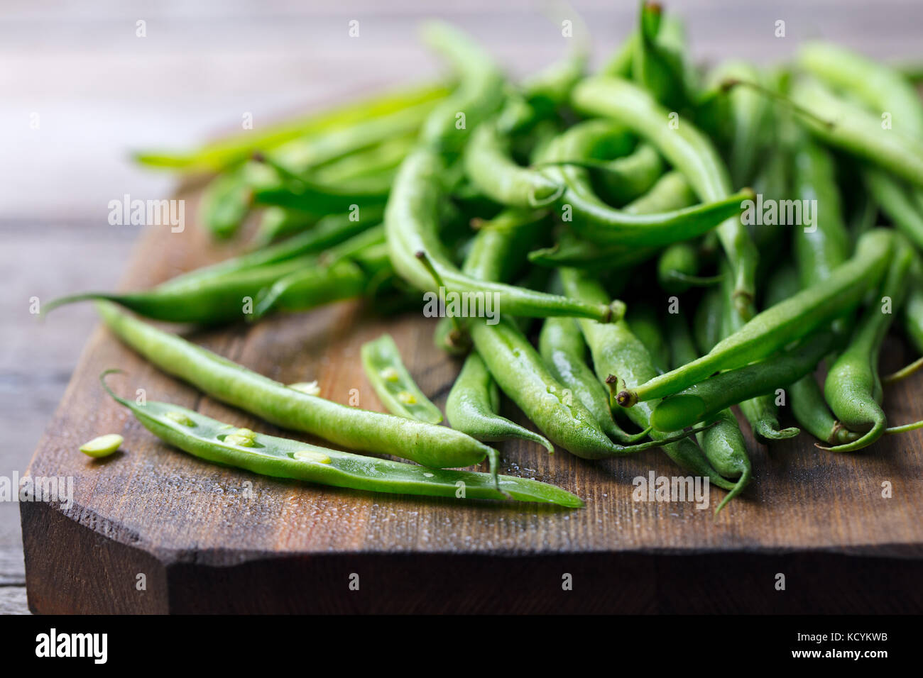 Green beans on wooden cutting board. Go green concept - Stock Image