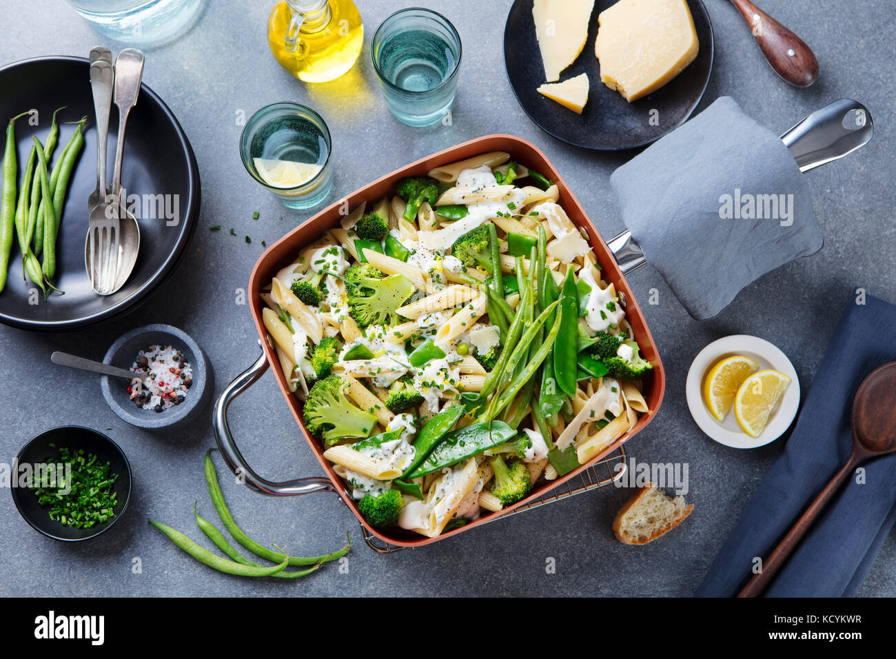 Pasta with green vegetables and creamy sauce in copper saucepan. Grey stone background. Top view. - Stock Image