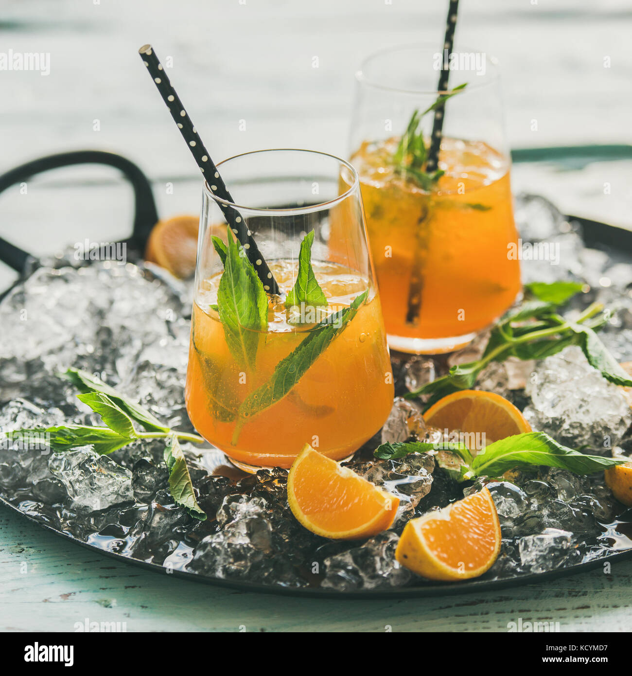 Refreshing cold alcoholic summer cocktail with orange and peppermint - Stock Image