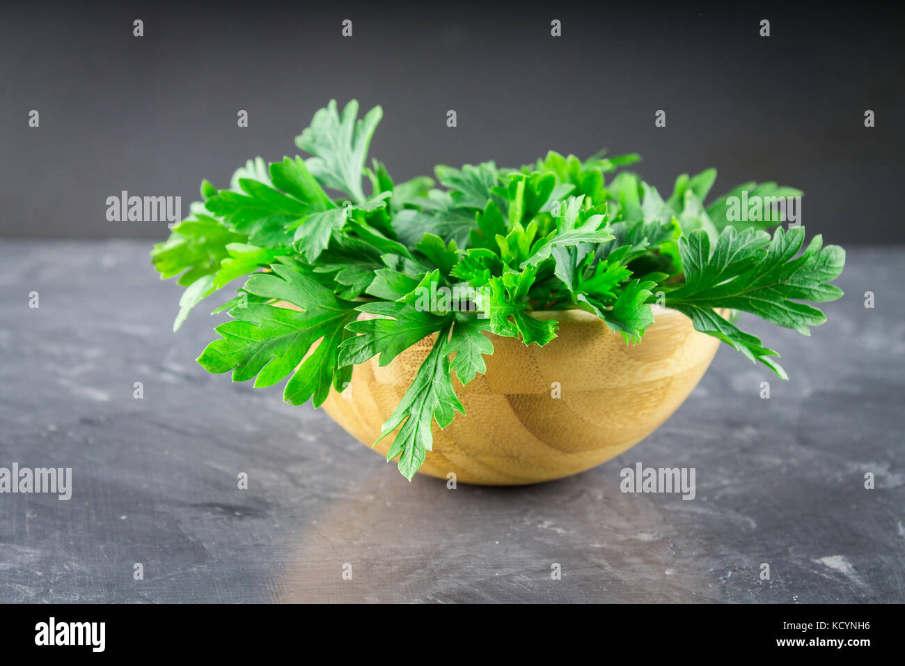 parsley in a wooden bowl on a gray background. - Stock Image