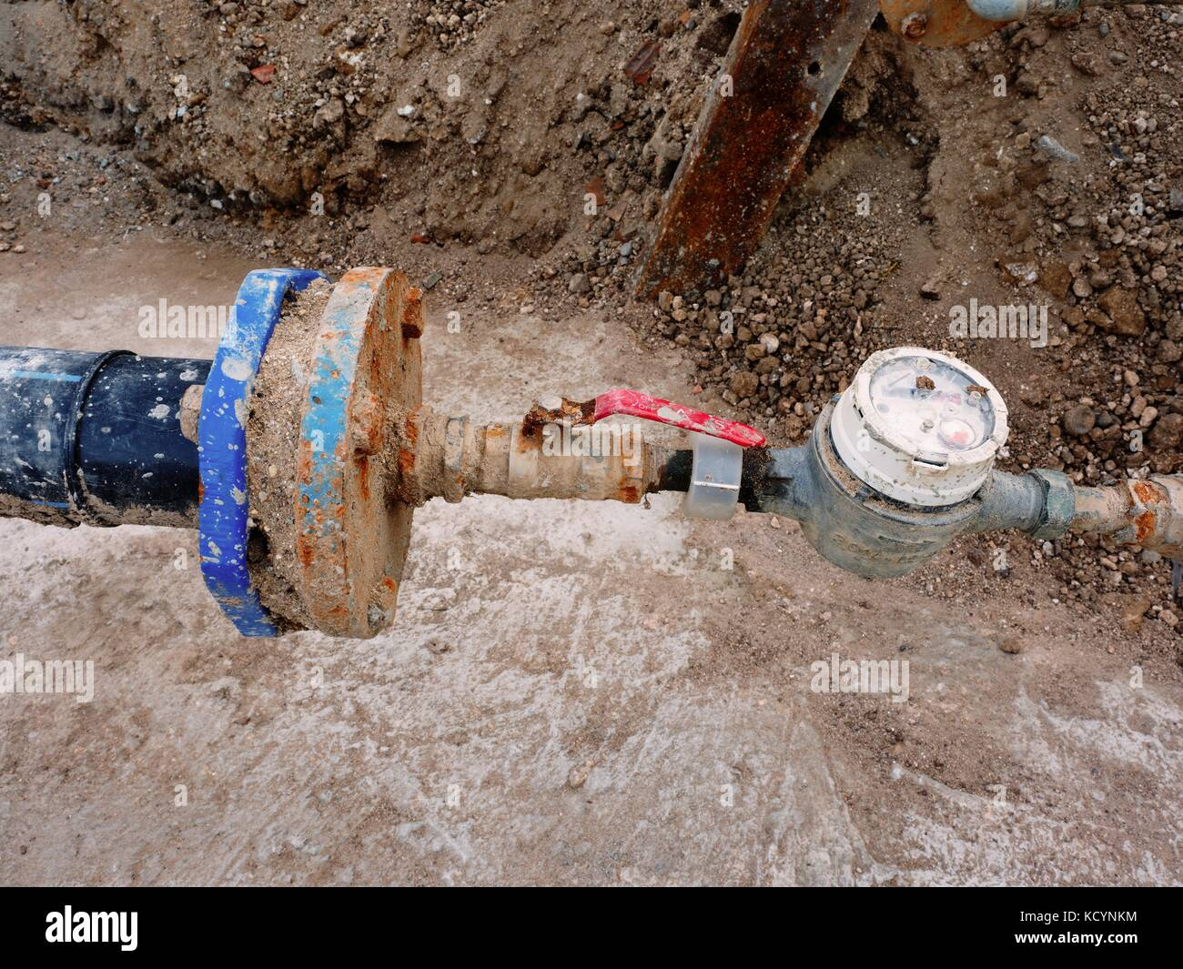 Old drink waser pipe, hydrometer and  shut-off valve  on  plastic tube. Repairing of drink water system. Open excavation - Stock Image