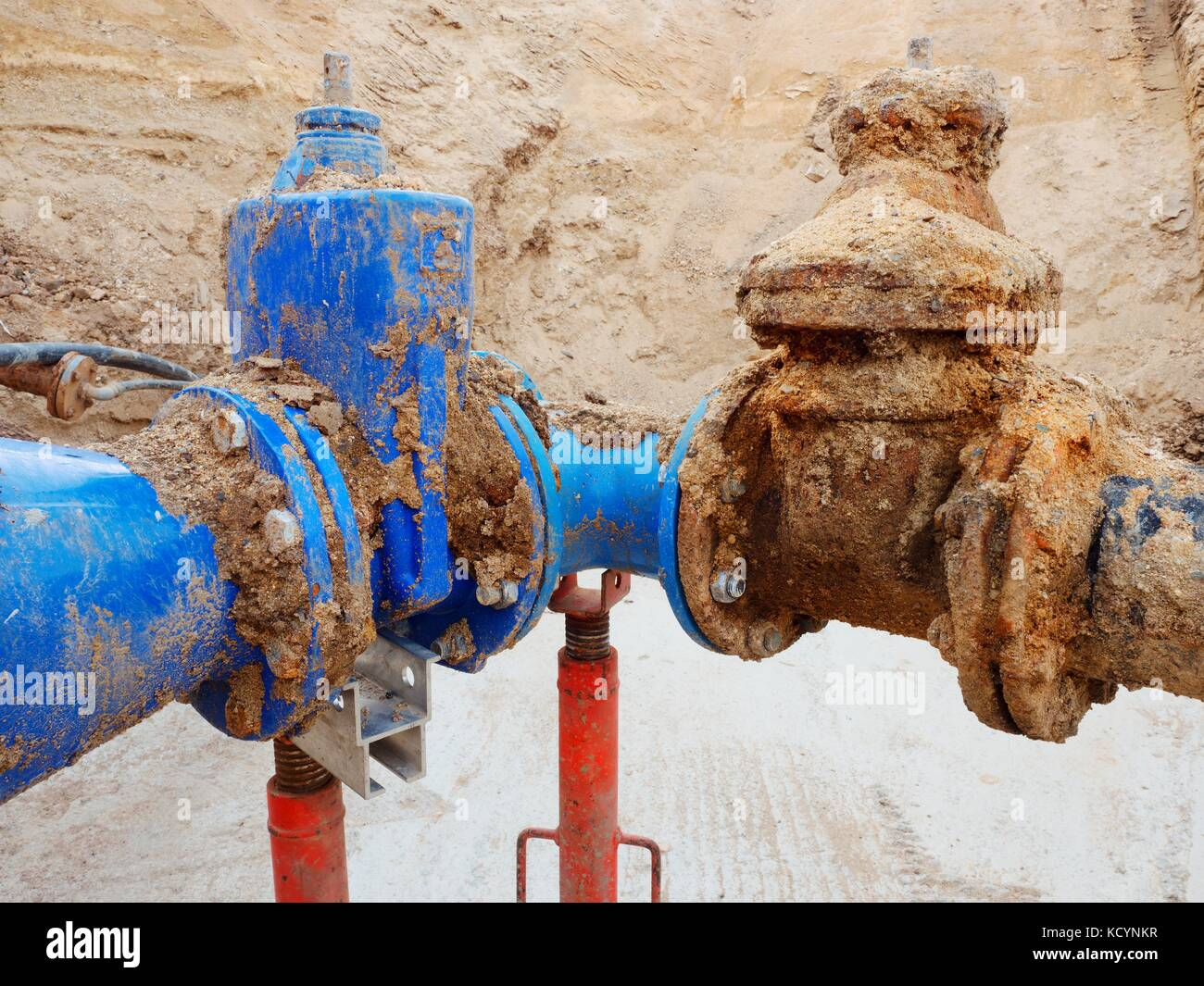 Old big drink water pipes joined with new blue gate valves and reduction joint members. Finished repaired piping - Stock Image