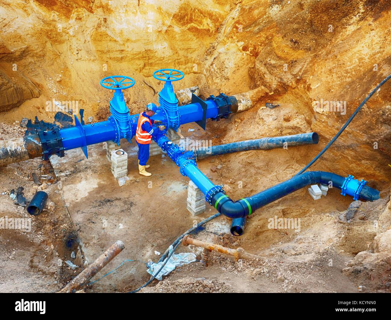 Technical expert underground at  gate valve on 500mm drink water pipes joined with new black waga multi joint members - Stock Image