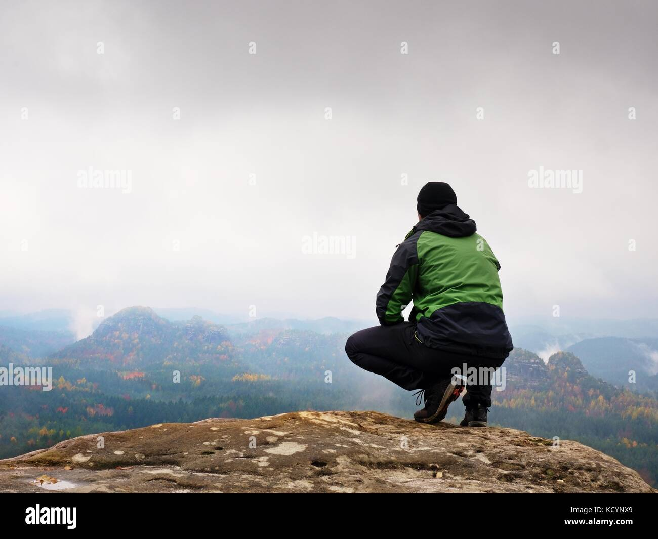 Tourist in red cap and  green black sportswear in squatting position on a rock, enjoy autumn scenery. Long valley - Stock Image