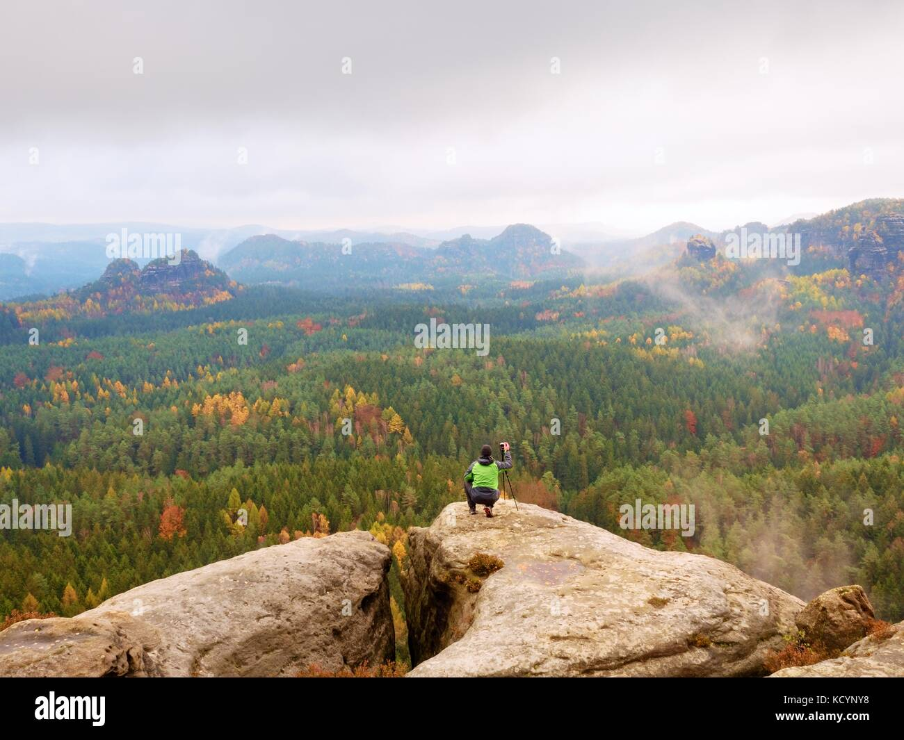 Hobby photographer takes picture of spring nature park from sharp rocks. Hiker in green jacket stay with camera - Stock Image