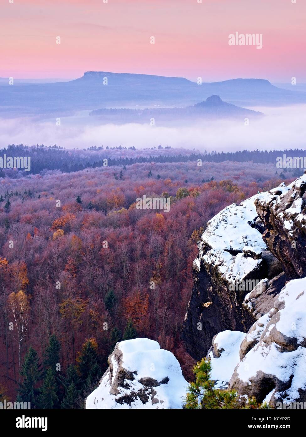 First powder snow cover on sandstone rocks above valley park. Heavy mist in valley bellow view point. Chilly autumnal - Stock Image