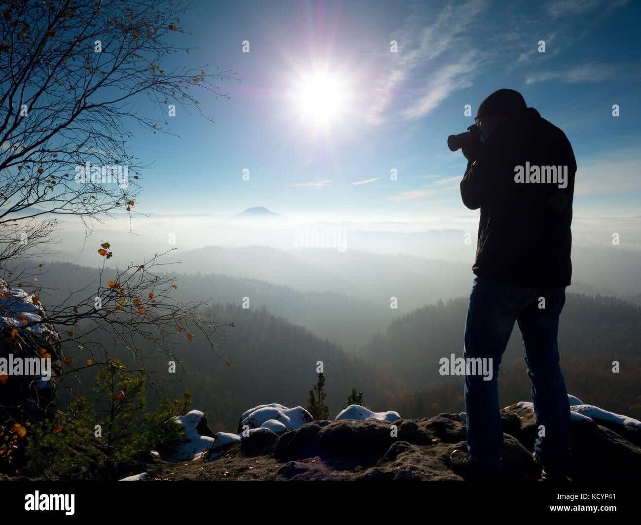 Professional photographer takes photos with mirror camera on peak of snowy rock.  Freeze fall day. Dreamy landscape, - Stock Image