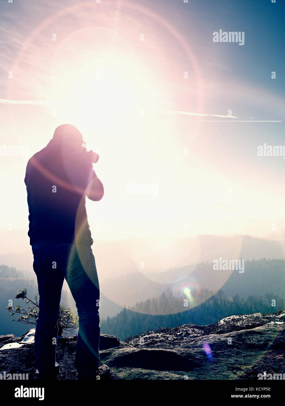 Tall  man is taking photo by mirror camera on neck. Snowy rocky peak of mountain. Professional photographer takes - Stock Image