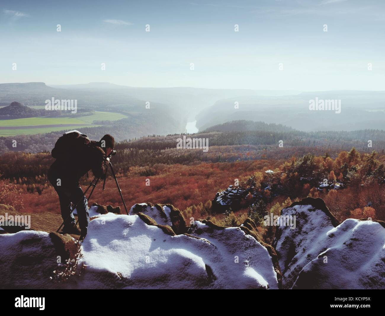 Professional photographer takes photos with mirror camera and tripod on snowy peak. Dreamy fogy landscape, spring - Stock Image