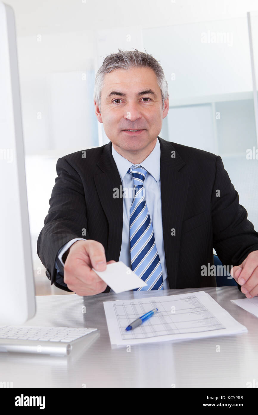 Senior Business Man Offering Visiting Card At Desk In Office Stock ...