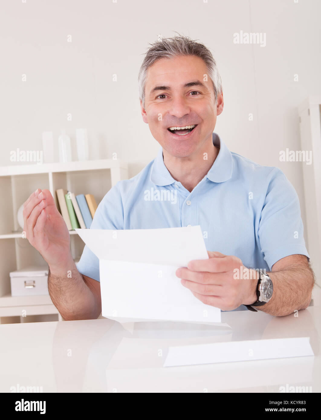 Happy Mature Man Holding Paper At Home - Stock Image