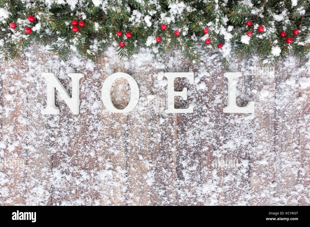Christmas border out of snow covered natural Christmas tree fir twigs, red berries and noel written with white wood - Stock Image