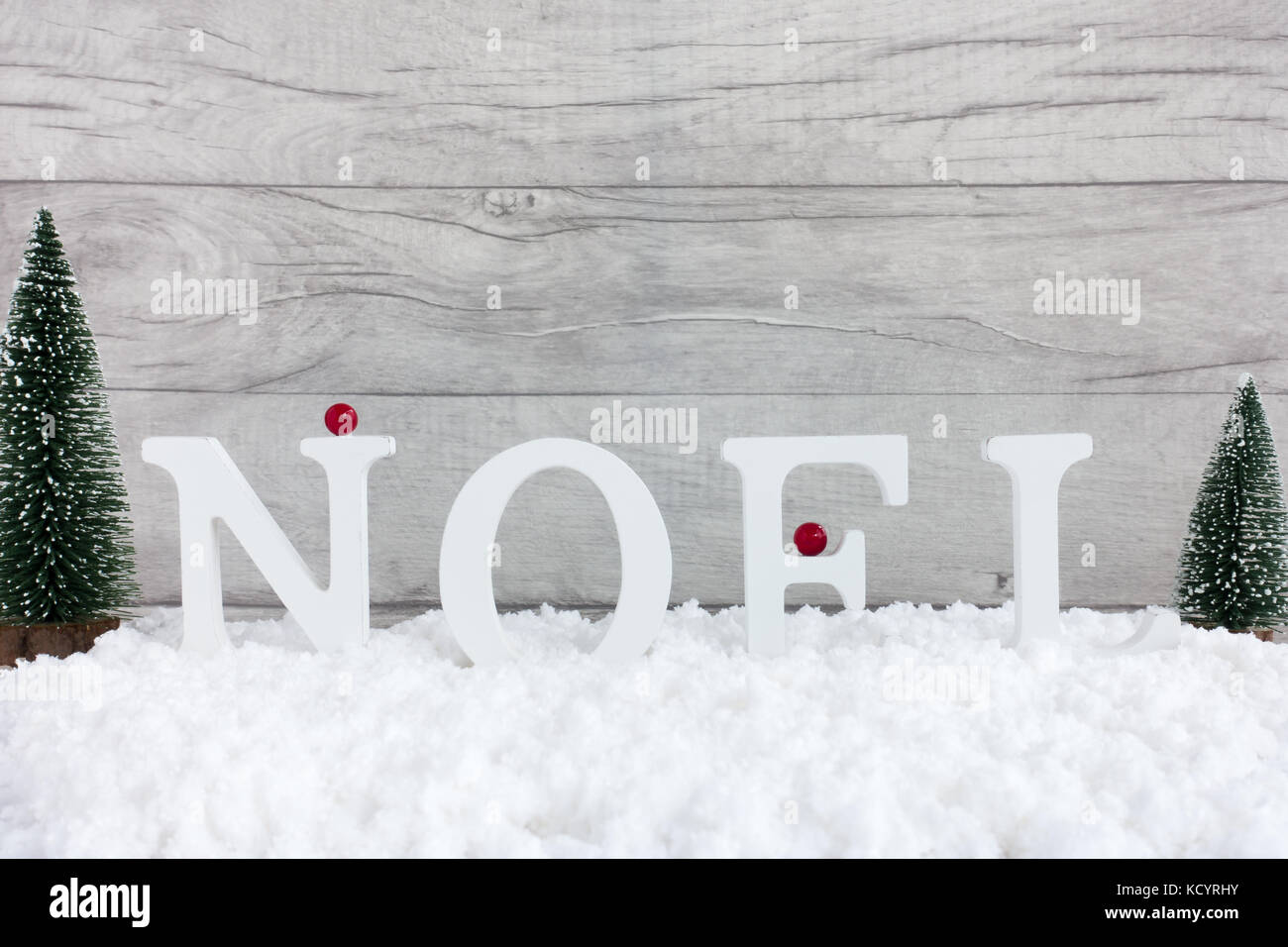 Winter scene with christmas trees and Noel written in wooden letters standing in snow and gray wooden background. - Stock Image