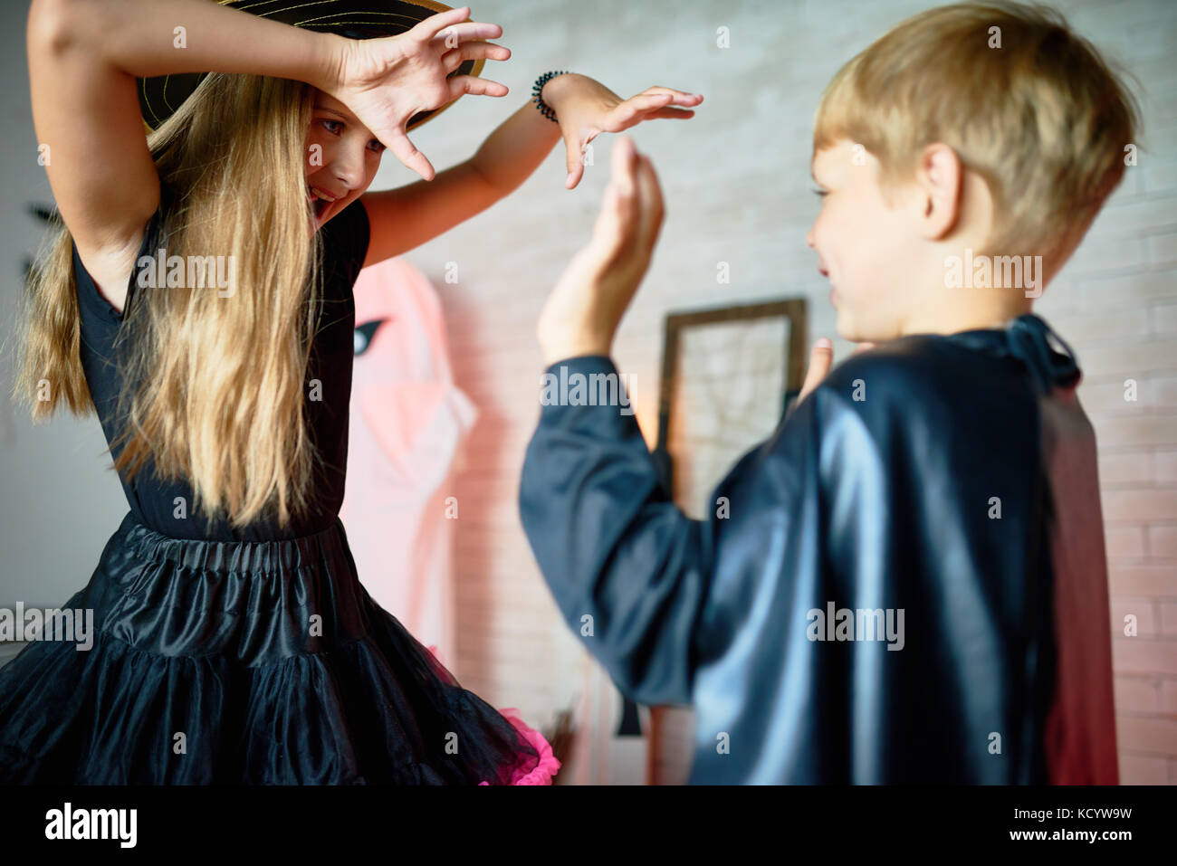 Portrait of teenage girl wearing witch costume trying to scare little boy on Halloween - Stock Image