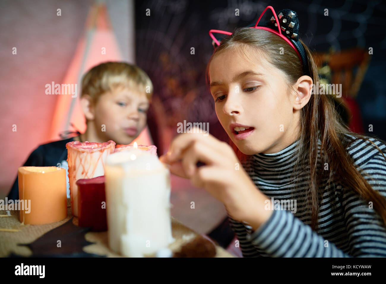 Portrait of pretty little girl lighting up candles on Halloween in decorated room, little boy wearing costume in - Stock Image