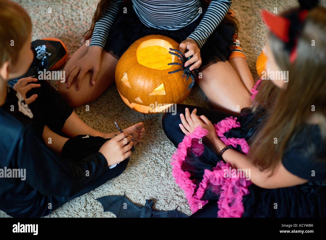 Above view of three children wearing Halloween costumes playing magic ritual with pumpkin lantern sitting on floor - Stock Image