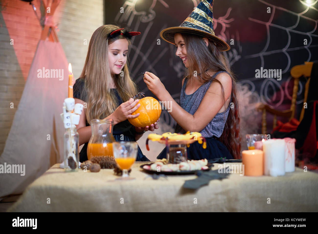 Cheerful little girls wearing Halloween costumes having fun at home party: they playing with toy spiders and enjoying - Stock Image