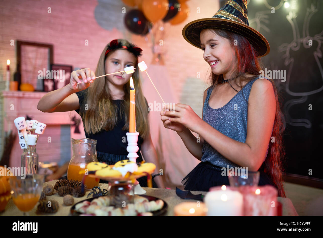 Two joyful friends wearing Halloween costumes making fried marshmallows with help of candle flame while enjoying - Stock Image