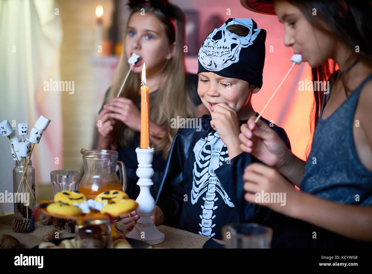 Portrait of handsome little boy wearing skeleton costume enjoying tasty fried marshmallows while celebrating Halloween - Stock Image