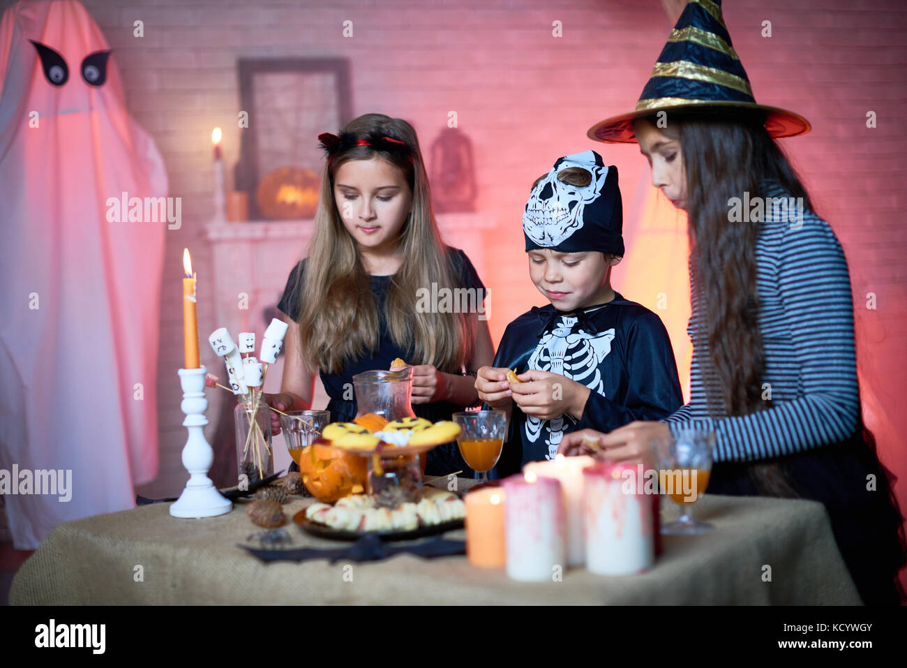 Cute little friends in fancy costumes gathered together at Halloween home party and stuffing their faces with tasty - Stock Image