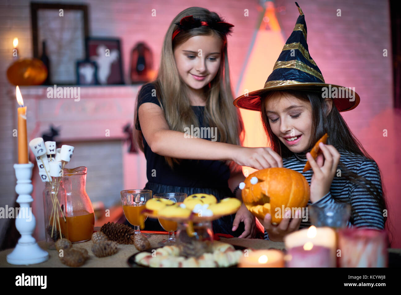 Pretty little sisters wearing fancy costumes decorating living room for Halloween party and anticipating arrival - Stock Image