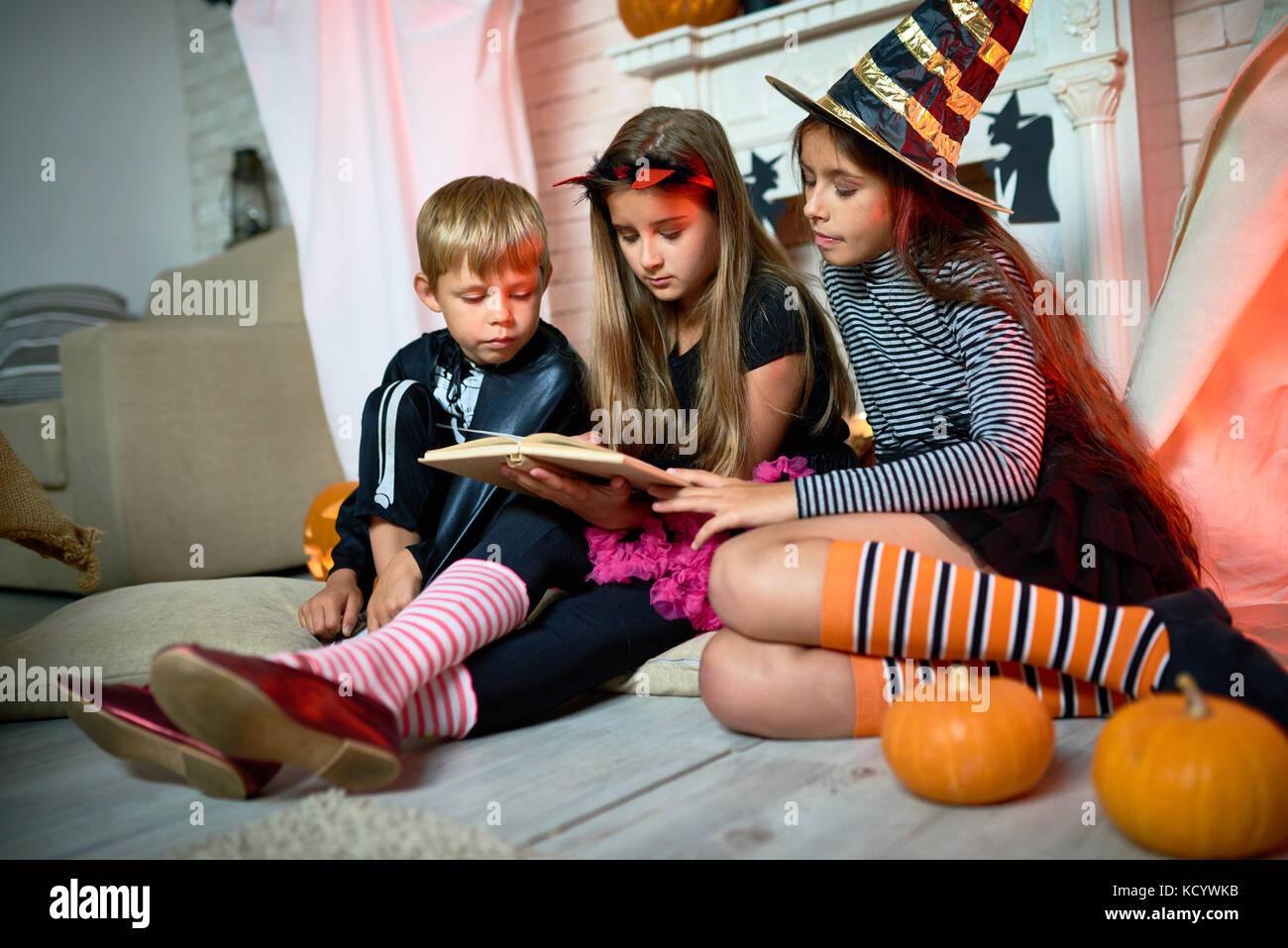 Group of cute kids wearing Halloween costumes gathered together at living room decorated for holiday and reading - Stock Image